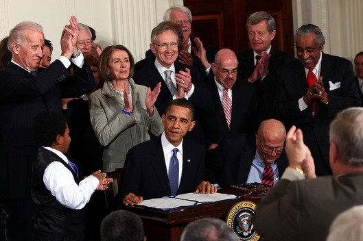 U.S. President Barack Obama (C) is applauded after signing the Affordable Health Care for America Act during a ceremony with fellow Democrats in the East Room of the White House March 23, 2010.