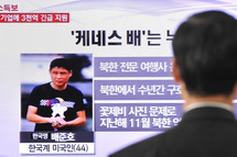 A passerby watches a local television broadcast in Seoul on May 2, 2013 showing a report and picture of Kenneth Bae (L), a Korean-American tour operator detained in North Korea. North Korea said on May 2 it had sentenced a Korean-American tour operator to 15 years' hard labour for 'hostile acts', stoking tensions with the United States, which had pleaded for his release.