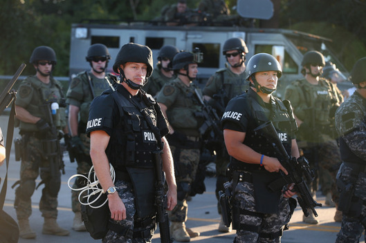 FERGUSON, MO - AUGUST 12:  Police take up position to control demonstrators who were protesting the killing of teenager Michael Brown on August 12, 2014 in Ferguson, Missouri. Brown was shot and killed by a police officer on Saturday in the St. Louis suburb of Ferguson. Ferguson has experienced two days of violent protests since the killing but, tonight's protest was peaceful.  (Photo by Scott Olson/Getty Images)
