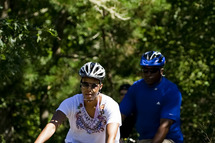 First Lady Michelle Obama (L) rides her bike in Manuel F. Correllus State Forest in West Tisbury, Massachusetts, August 23, 2011, during their family vacation to Martha's Vineyard.  AFP PHOTO/Jim WATSON (Photo credit should read JIM WATSON/AFP/Getty Images)