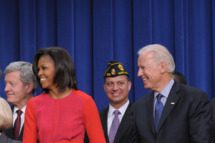First Lady Michelle Obama clasps the hand of Vice President Joe Biden as US President Barack Obama speaks before signing a bill which provides tax credits to companies to put veterans back to work on November 21, 2011 in the South Court Auditorium, next to the White House in Washington, DC..