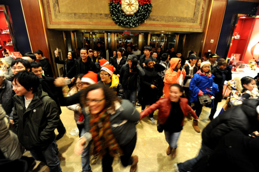 "People rush into the entrance of Macy's department store as they open at midnight (0500 GMT) on November 25, 2011 in New York to begin the ""Black Friday"" shopping weekend.   AFP PHOTO/Stan HONDA (Photo credit should read STAN HONDA/AFP/Getty Images)"