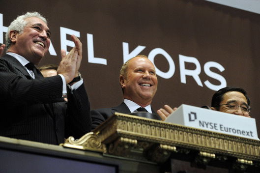 Michael Kors, chief creative officer of Michael Kors Holdings Ltd., center, rings the opening bell at the New York Stock Exchange (NYSE) in New York, U.S., on Thursday, Dec.15, 2011.