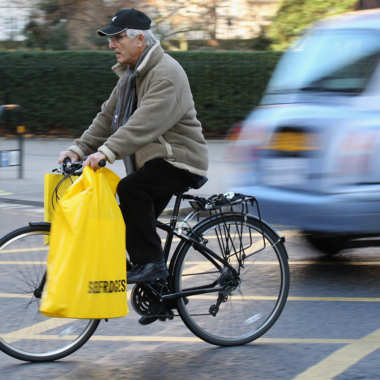 A man cycles with shopping bags on his bike .