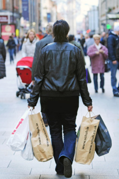 A shopper carries bags of purchases along Henry Street in Dublin, Ireland, on Tuesday, Dec. 27, 2011. Ireland, which spent this year trying to prove to investors its finances weren't like euro partners closer to the Mediterranean, may have to pay Greek and Portuguese rates next year to return to the credit market. Photographer: Aidan Crawley/Bloomberg via Getty Images