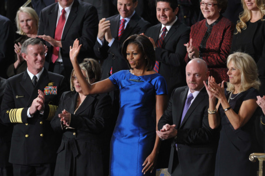 US First Lady Michelle Obama (R) waves from the gallery of the US House of Representatives prior to US President Barack Obama's State of the Union address on January 24, 2012 on Capitol Hill in Washington, DC. From left are: Admiral William McRaven; Jackie Bray; Michelle Obama; US astronaut Mark Kelly, husband of shot US Rep. Gabrielle Giffords; Dr. Jill Biden, wife of US Vice President Joe Biden; and Ashleigh Berg.   AFP PHOTO / Mandel NGAN (Photo credit should read MANDEL NGAN/AFP/Getty Images)