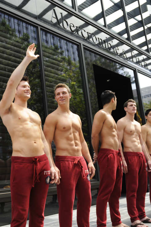 Abercrombie & Fitch (A&F) models beckon the public to take pictures with them outside the A&F store in Knightsbridge, a Singapore shopping mall on December 9, 2011.  A&F's first Singapore store will open to the public on December 15.