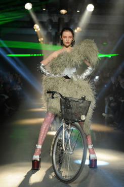 A model a rides a bicycle on the runway during the Vivienne Westwood Ready-To-Wear Fall/Winter 2012 show as part of Paris Fashion Week at Docks en Seine on March 3, 2012 in Paris, France.