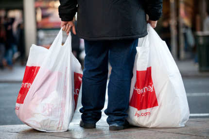 A man carrying two shopping bags waits to cross 6th Avenue on December 26, 2011 in New York City.
