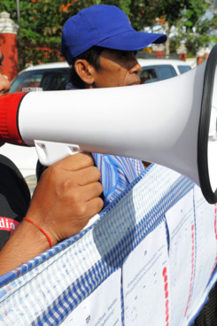 A Cambodian man shouts slogans as people hold a 230-meters long petition