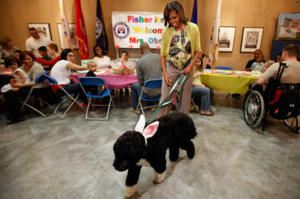 "To kick off the Month of the Military Child, first lady Michelle Obama and her dog Bo participate in a pre-Easter celebration with military families and children at the Fisher House on Walter Reed National Military Medical Center April 4, 2012 in Bethesda, Maryland. The Fisher Houses are ""comfort homes"" that enable family members to be close to their military loved one during hospitalization for an unexpected illness, disease, or injury. Obama delivered Easter candies, visited with military children and gave away tickets to the White House Easter Egg Roll during the visit."