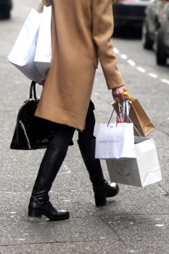 A shopper carries branded shopping bags from Harvey Nichols and the Prada SpA store as she walks along Old Bond Street in London, U.K. on Wednesday, Feb. 29, 2012. Bank of England Deputy Governor Charles Bean yesterday cautioned lawmakers against putting too much weight on positive signs in the economy. Photographer: Simon Dawson/Bloomberg via Getty Images