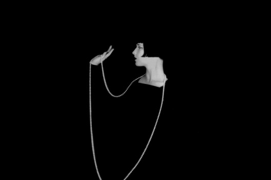 1929: American actress Louise Brooks (1906 - 1985) wearing a long necklace which stands out starkly against a black background.