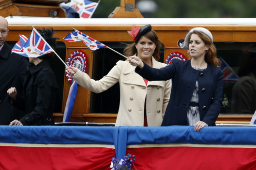 LONDON, ENGLAND - JUNE 03:  Princess Beatrice (R)  and Princess Eugenie wave from a barge in a flotilla of 1,000 vessels during the Diamond Jubilee Thames River Pageant on June 3, 2012 in London, England. For only the second time in its history the UK celebrates the Diamond Jubilee of a monarch. Her Majesty Queen Elizabeth II celebrates the 60th anniversary of her ascension to the throne. Thousands of well-wishers from around the world have flocked to London to witness the spectacle of the weekend's celebrations. The Queen along with all members of the royal family will participate in a River Pageant with a flotilla of a 1,000 boats accompanying them down The Thames, the star studded free concert at Buckingham Palace, and a carriage procession and a service of thanksgiving at St Paul's Cathedral.  (Photo by Matt Dunham - WPA Pool/Getty Images)