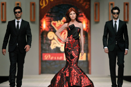 In this photo taken Friday, June 8, 2012, Russian ex-spy Anna Chapman, center, walks a Turkish catwalk flanked by two men posing as secret service agents at a fashion show in Antalya, Turkey. The 30-year-old Chapman was deported from the United States in 2010 along with nine other Russian sleeper agents.