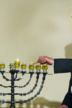David Ben-Gurion's grandson Yariv Ben-Eliezer lights the Menorah during the Hanukkah reception at White House in Washington, DC, December 15, 2008.     AFP PHOTO/Jim WATSON (Photo credit should read JIM WATSON/AFP/Getty Images)
