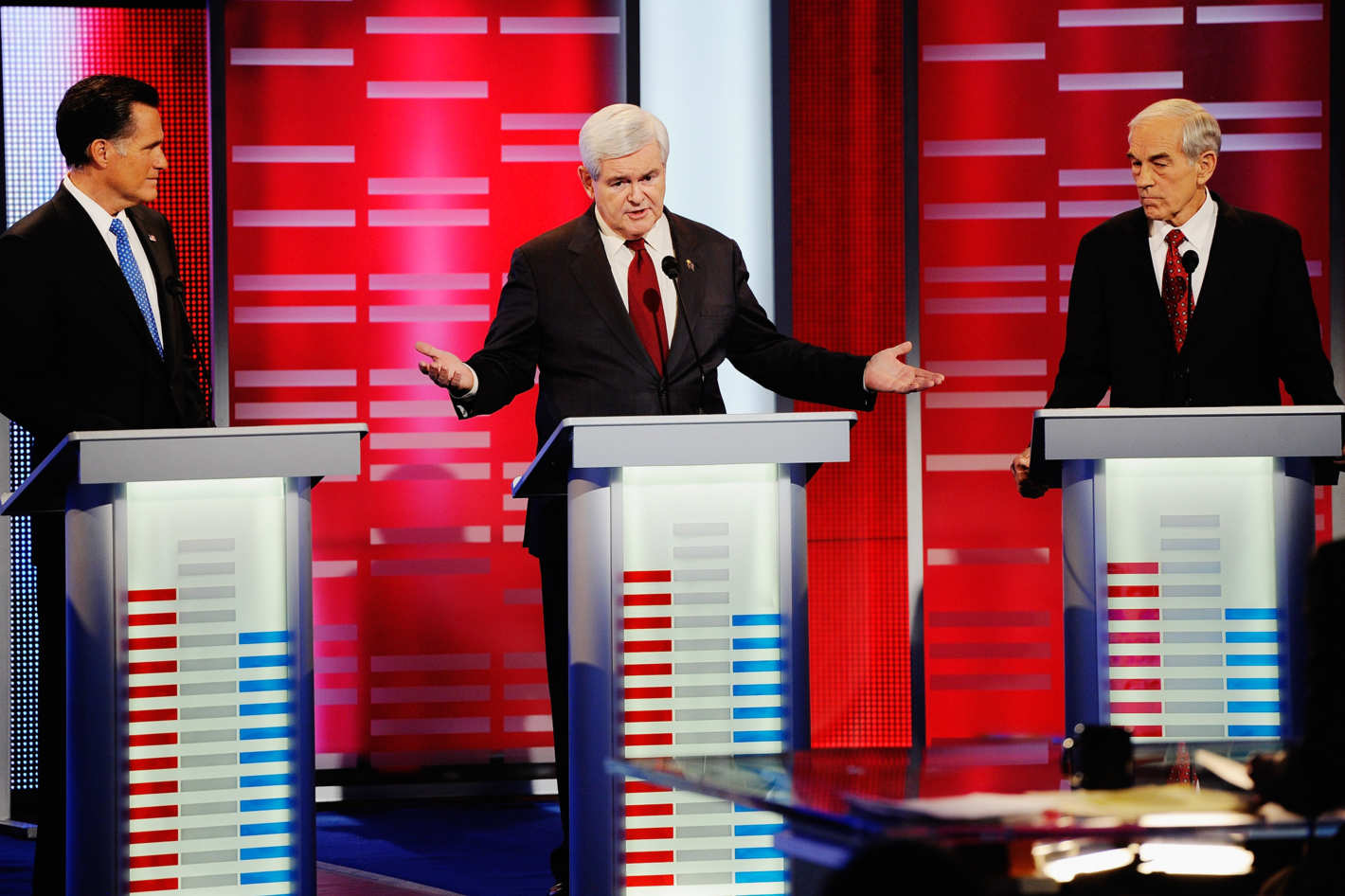DES MOINES, IA - DECEMBER 10:  Former speaker of the House Newt Gingrich (C) speaks while former Massachusetts Gov. Mitt Romney (L) and U.S. Rep. Ron Paul (R-TX) look on during th ABC News GOP Presidential debate on the campus of Drake University on December 10, 2011 in Des Moines, Iowa. Rivals were expected to target front runner Gingrich in the debate hosted by ABC News, Yahoo News, WOI-TV, The Des Moines Register and the Iowa GOP.  (Photo by Kevork Djansezian/Getty Images)