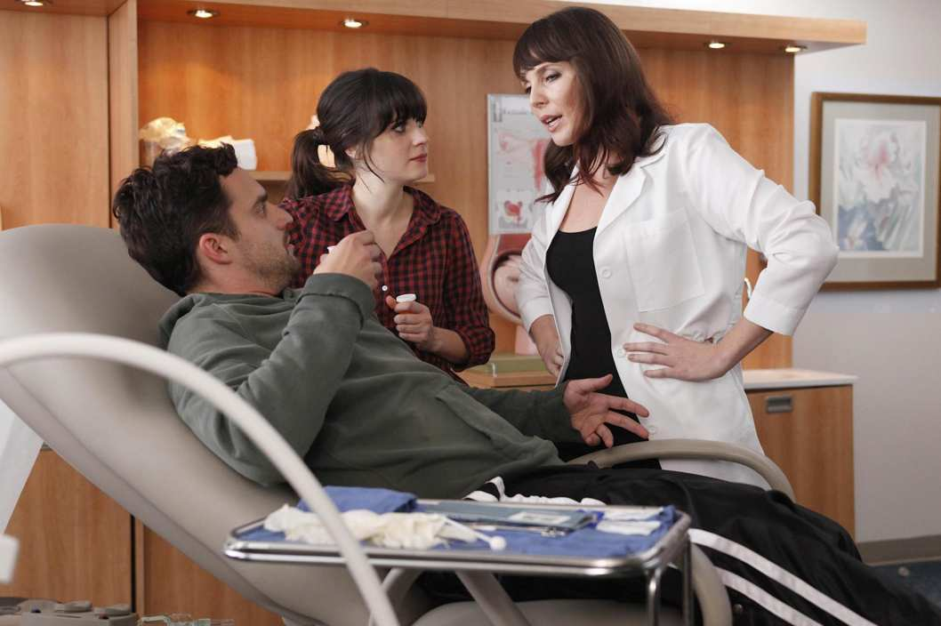 "NEW GIRL:  When Nick (Jake Johnson, L) is hurt playing touch football, Jess (Zooey Deschanel, C) discovers he doesn't have insurance and brings him to her friend (guest star June Diane Raphael, R) who is an OB-GYN in the ""Injured"" episode of NEW GIRL."
