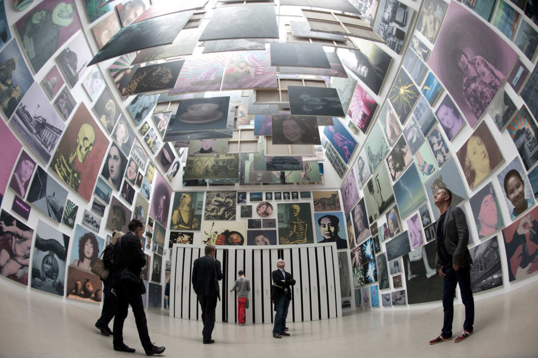 "Visitors look at paintings displayed in the installation ""Limited Art Project, 2011-2012"", consisting of 377 paintings, commissioned and produced by dOCUMENTA (13)"