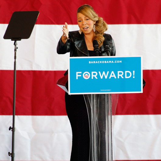In anticipation of First Lady Michelle Obama's arrival, singer Mariah Carey speaks to a crowd of Obama supporters in a hangar at the Charlotte Douglas International Airport in Charlotte, N.C. Monday Nov. 5, 2012.