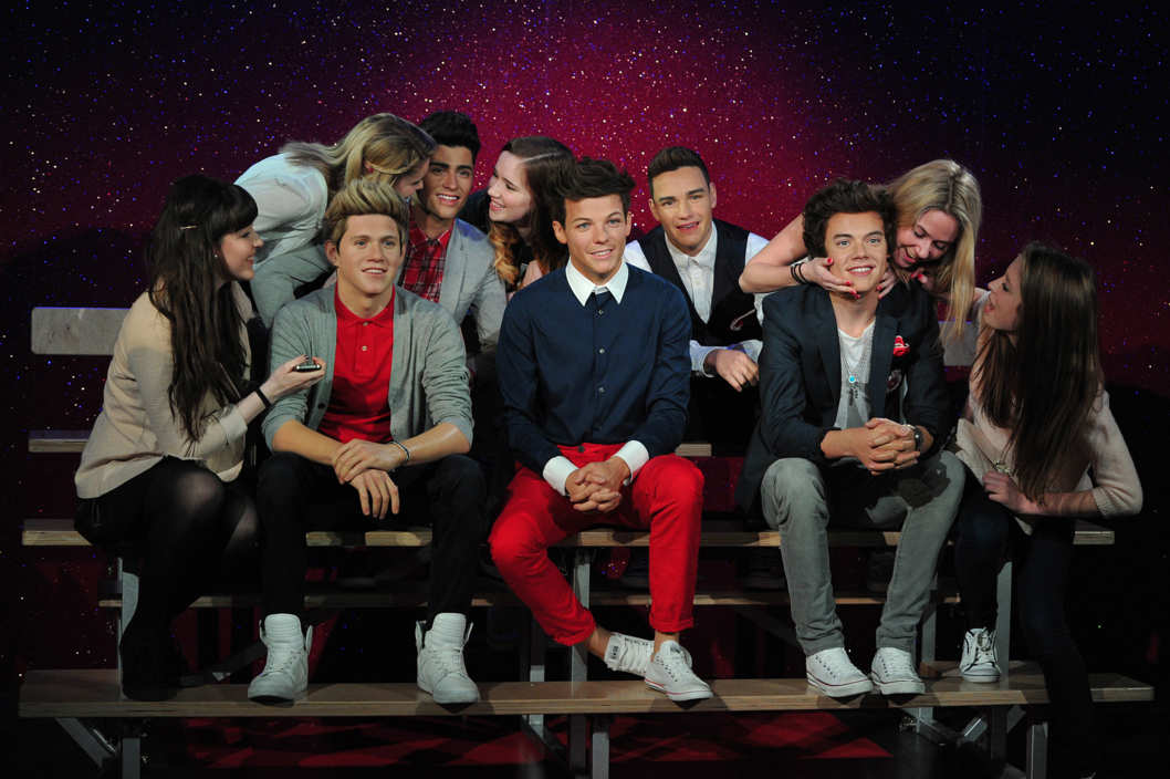 Fans pose for pictures with waxwork models of English-Irish boy band 'One Direction' during a photocall at Madame Tussauds in central London, on April 18, 2013. The wax figures will stay in London for 12 weeks before embarking on a tour that will next visit Madame Tussauds New York and Sydney. AFP PHOTO/CARL COURT        (Photo credit should read CARL COURT/AFP/Getty Images)