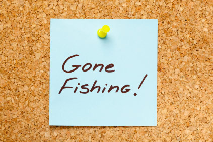 GONE FISHING! written on a blue sticky note on an office cork bulletin board.