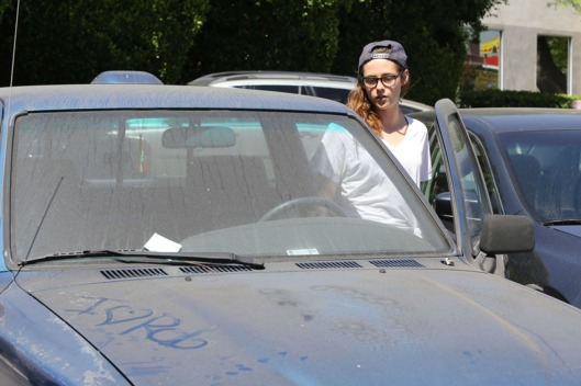 "Kristen Stewart entering her truck, which has ""I Love Rob"" written across the hood."