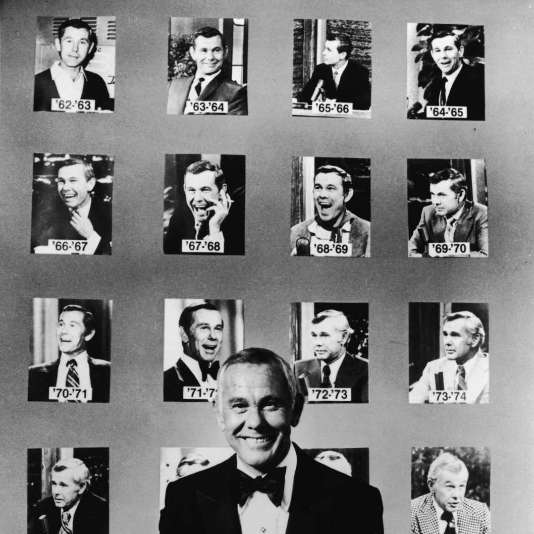 American talk show host and comedian Johnny Carson (1925 - 2005) wears a tuxedo and poses in front of portraits of him from his first twenty years as host of the NBC late night talk show 'The Tonight Show,' early 1980s. (Photo by NBC Television/Getty Images)
