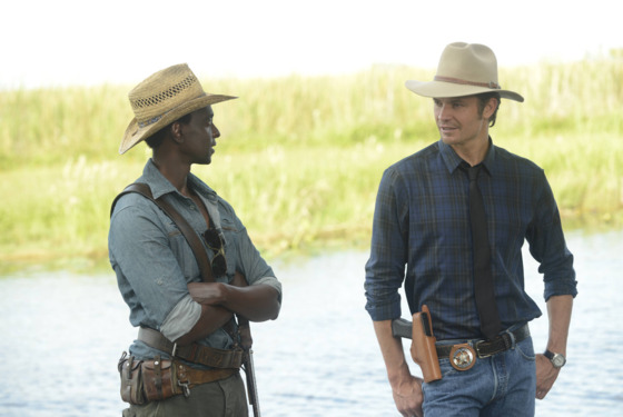 JUSTIFIED -- A Murder of Crowes -- Episode 501 (Airs Tuesday, January 7, 10:00 pm e/p) -- Pictured: (L-R) Edi Gathegi as Jean Baptiste, Timothy Olyphant as Deputy U.S. Marshal Raylan Givens -- CR: Guy D'Alama/FX