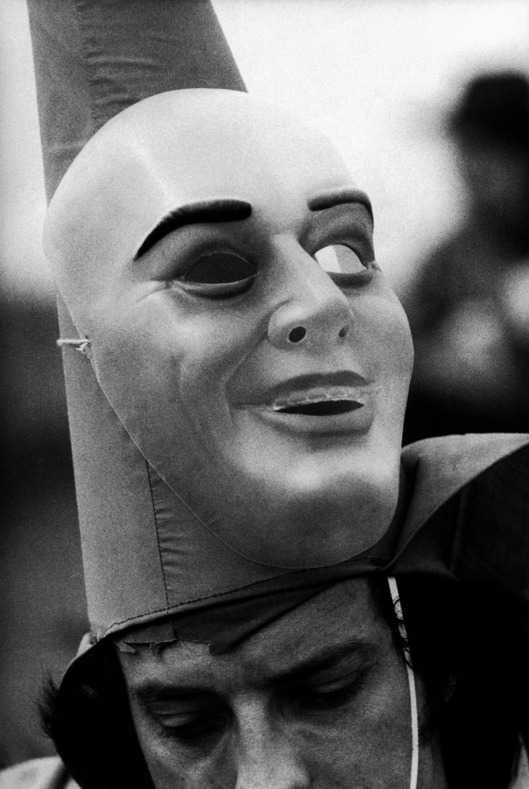 ca. 1976, Mamou, Louisiana, USA --- The mask of reveler in a Cajun Marti Gras celebration is up around his pointed hat. Mamou, Louisiana. --- Image by ? Philip Gould/Corbis