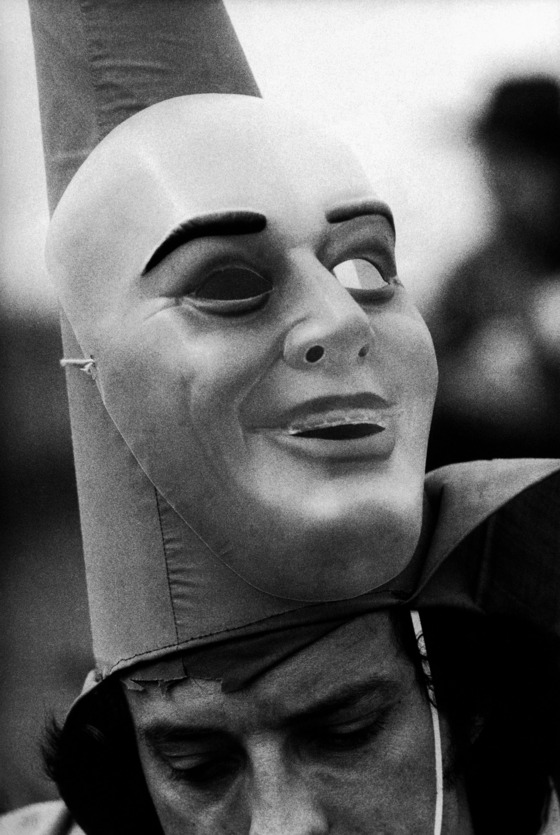 ca. 1976, Mamou, Louisiana, USA --- The mask of reveler in a Cajun Marti Gras celebration is up around his pointed hat. Mamou, Louisiana. --- Image by © Philip Gould/Corbis
