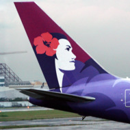 A worker stands next to the tail of a Hawaiian Airlines aircraft parked at Manila international airport on June 16, 2008.    AFP PHOTO/TED ALJIBE (Photo credit should read TED ALJIBE/AFP/Getty Images)