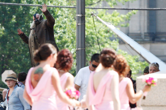 "PITTSBURGH, PA  - JULY 30: Actor Tom Hardy (background), who plays the villian Bane, waves to bridesmaids across the street while on the set of ""The Dark Knight Rises"" filming near the Carnegie Mellon University Software Engineering Institute Building in the neighborhood of Oakland on July 30, 2011 in Pittsburgh, Pennsylvania. (Photo by Jared Wickerham/Getty Images)"