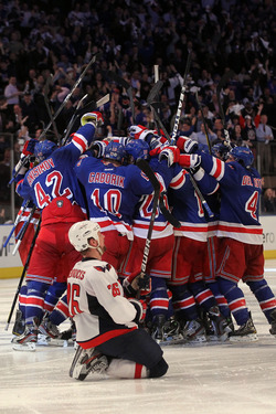 NEW YORK, NY - MAY 07: Marc Staal #18 of the New York Rangers celebrates with his teammates after scoring the winning goal in overtime against Braden Holtby #70 of the Washington Capitals as Matt Hendricks #26 of the Washington Capitals slides to the ice after Game Five of the Eastern Conference Semifinals during the 2012 NHL Stanley Cup Playoffs at Madison Square Garden on May 7, 2012 in New York City. The New York Rangers defeated the Washington Capitals in overtime 2-3. (Photo by Bruce Bennett/Getty Images)