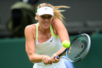 Russia's Maria Sharapova plays a shot during her first round women's singles match against Australia's Anastasia Rodionova on the first day of the 2012 Wimbledon Championships tennis tournament at the All England Tennis Club in Wimbledon, southwest London, on June 25, 2012.