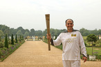 In this handout image provided by LOCOG, Torchbearer 009 Mark Levy holds the Flame in the grounds of Hampton Court Palace during the final day on July 27, 2012 in London, England.