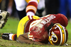 Robert Griffin III #10 of the Washington Redskins is injured as he fumbles a low snap in the fourth quarter against the Seattle Seahawks during the NFC Wild Card Playoff Game at FedExField on January 6, 2013 in Landover, Maryland.
