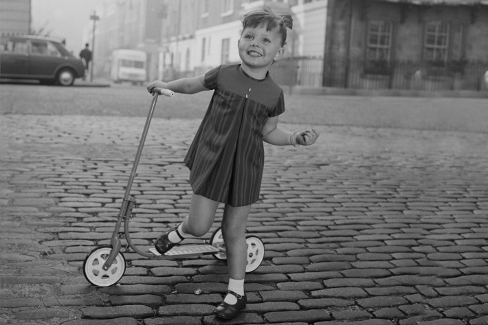 Little girl with a scooter on a cobblestone street — The Strategist reviews the best scooters for kids