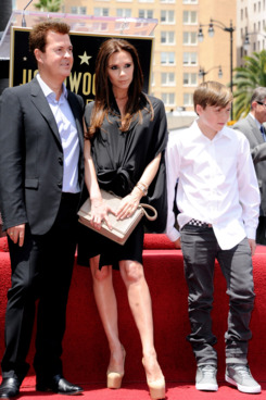 Victoria Beckham, Brooklyn Beckham, and baby bump obscured by a bow.