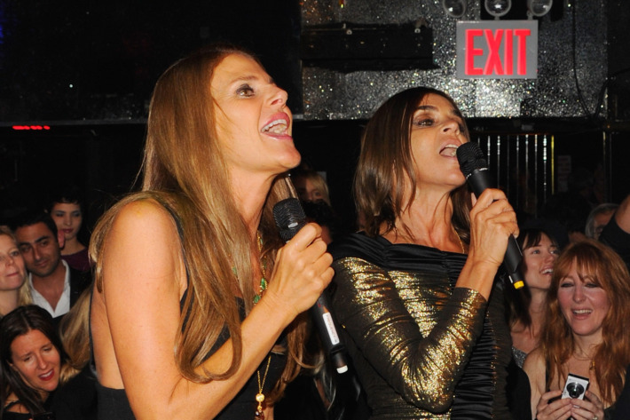 Anna Della Russo and Carine Roitfeld belt out a duet.