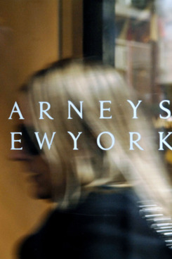 A Barneys New York logo is pictured as a woman enters their 5th Avenue store in New York, Tuesday, March 21, 2006.