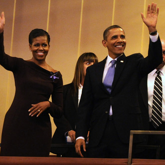U.S. President Barack Obama and first lady Michelle Obama wave to guests as they arrive in their box at the Kennedy Center for the Performing Arts to attend the Let Freedom Ring Celebration on January 16, 2012 in Washington, DC.