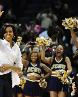 First lady Michelle Obama waves to the crowd as members of the Johnson C. Smith University cheerleaders cheer during the Let's Move! pre-game event during the CIAA Tournament at Time Warner Cable Arena on Friday, March 2, 2012 in Charlotte, North Carolina.
