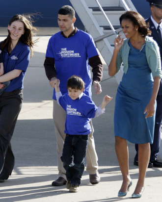 First lady Michelle Obama walks with Cpl. Tiffany Garcia and her husband Omar Garcia and their children Joel, 4, left, and Omar, 5, from The Mission Continues during her arrival at Lambert St. Louis International Airport, Monday, March 5, 2012, in St. Louis. The Mission Continues is a national nonprofit organization challenging post-9/11 veterans to serve and lead in their communities.