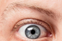 Closeup of a blue eye, of a Caucasian man, showing intricate details of the iris.