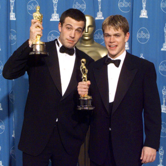 Matt Damon (R) and Ben Affleck (L) pose with their Oscars they won for Best Original Screenplay for