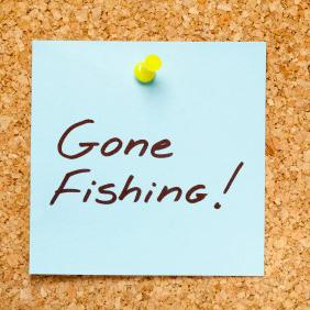 GONE FISHING! written on a blue sticky note on an office cork bulletin board.