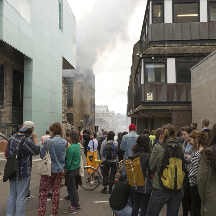Glasgow, United Kingdom. 23rd May 2014 -- Larger crowds start to gather from neighbouring offices. -- The Charles Rennie Mackintosh designed Glasgow School of art is currently on fire with emergency services crews in attendance.