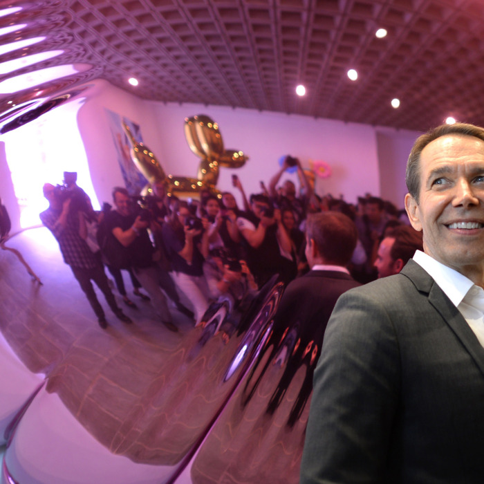 Artist Jeff Koons poses next to one of his sculptures during a press preview of