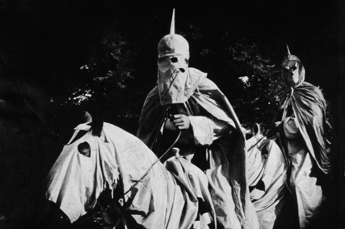 Actors costumed in the full regalia of the Ku Klux Klan ride on horses at night in a still from 'The Birth of a Nation,' the first-ever feature-length film, directed by D. W. Griffith, 1914.